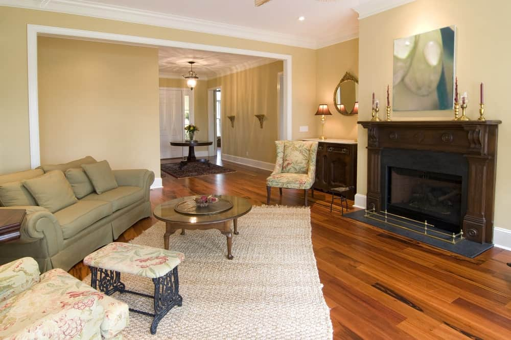 Elegant living room with classy seats and lovely hardwood flooring. The fireplace is just perfect together with the walls and flooring.