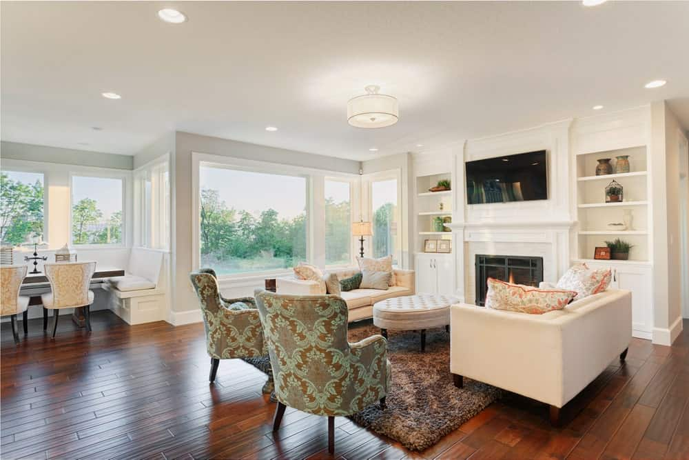 This living room offers elegant seats set on the hardwood flooring topped by a beautiful rug. There's a fireplace with a TV on top. The lights are lovely in this living room set.