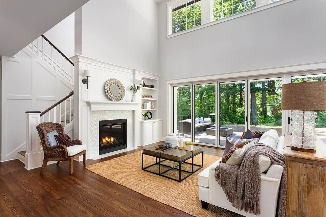 A simple yet classy living room featuring a hardwood flooring and a rug along with a fireplace and white couch.