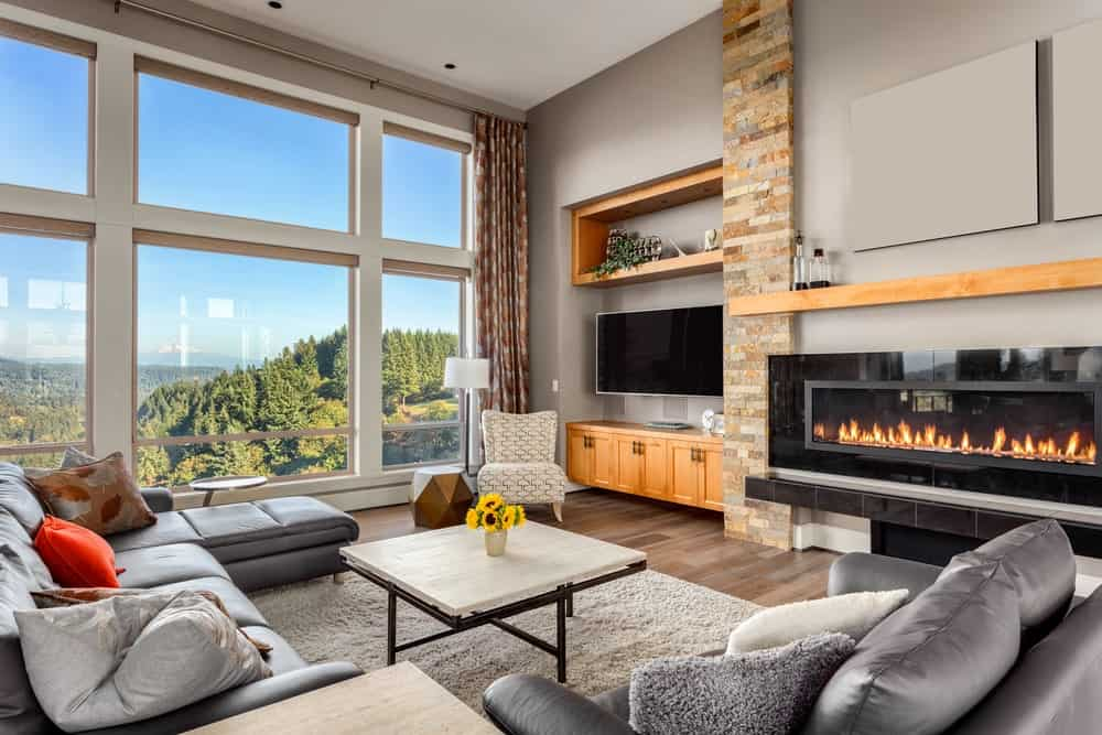 Large modish living room with glass windows overlooking the beautiful surroundings. The comfortable seats are paired with a stylish fireplace keeping the room warm.