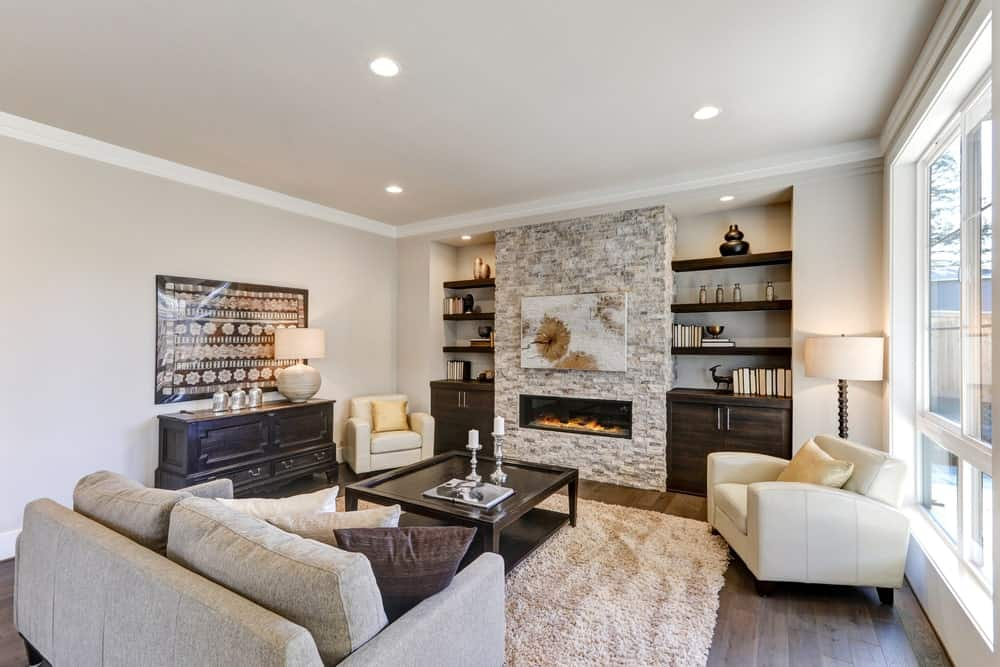 This living room features a stylish fireplace and beige walls. The hardwood flooring is topped by a white rug. The seats look gorgeous along with the center table.