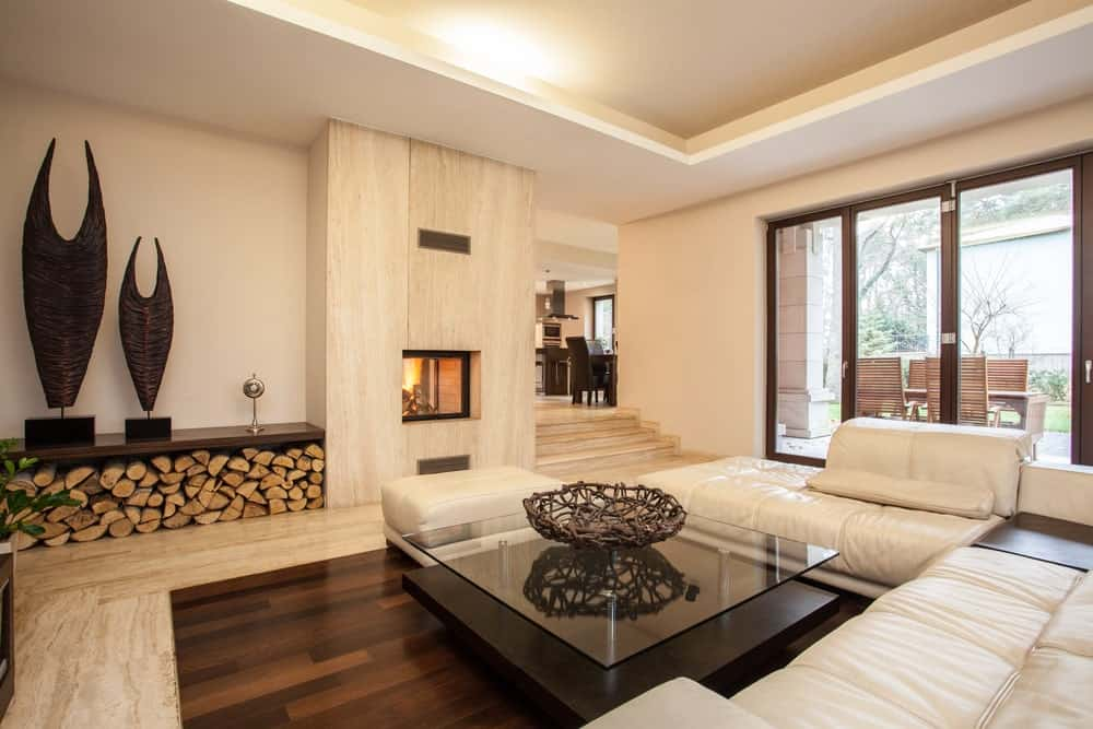 Large living room with stylish decorations and a fireplace. The sofa set looks so handsome together with the center table with a glasstop.