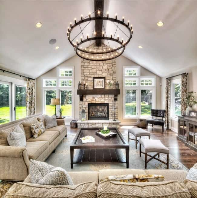 This living room offers a stunning chandelier along with comfortable seats set on a lovely rug. The fireplace adds class to the home's living room.