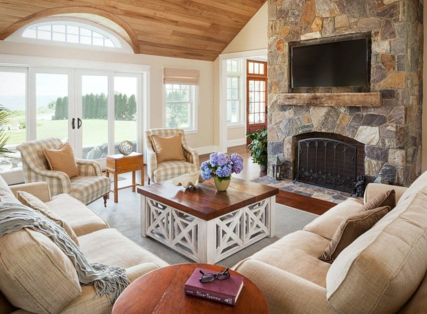 A rustic living room featuring modish and traditional cozy seats near the stylish fireplace.