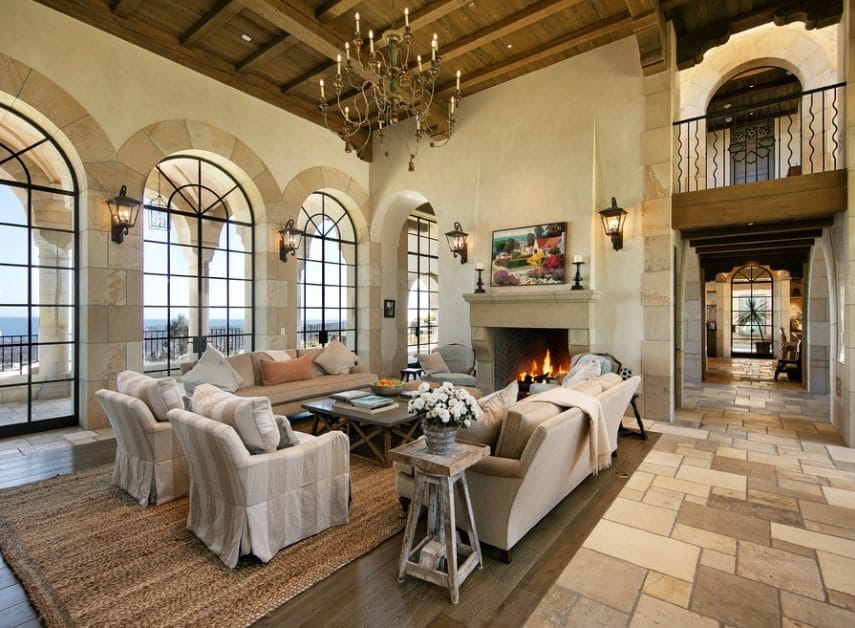 Large Mediterranean living room featuring stunning tiles flooring and a high ceiling lighted by a glamorous chandelier. The sofa set looks perfect together with the home's walls.
