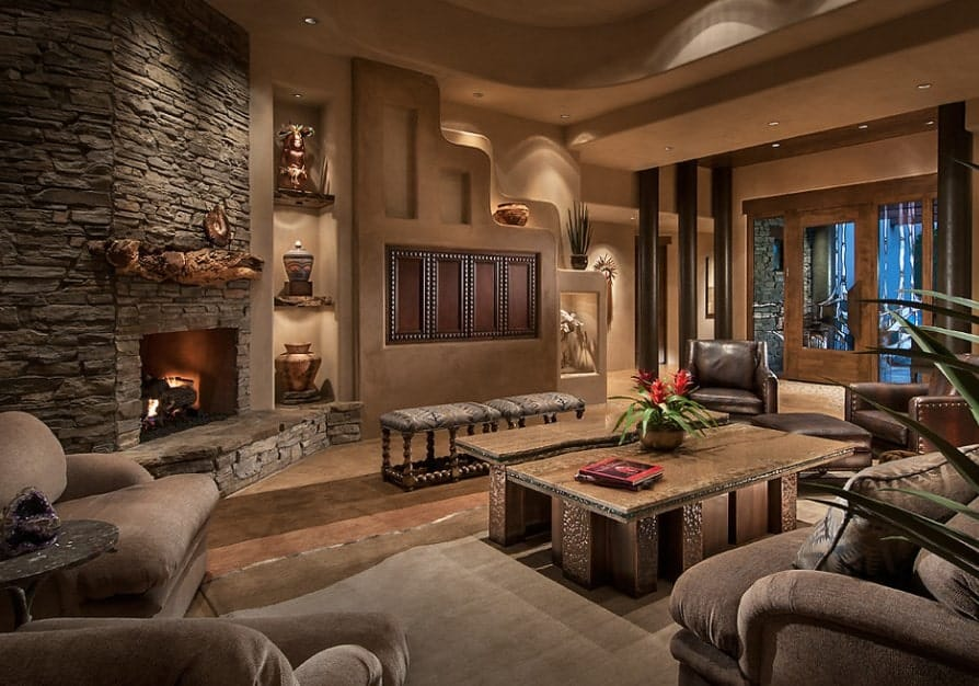 A stunning living room setup featuring classy seats, elegant tables and glamorous decorations. The fireplace is absolutely jaw-dropping.