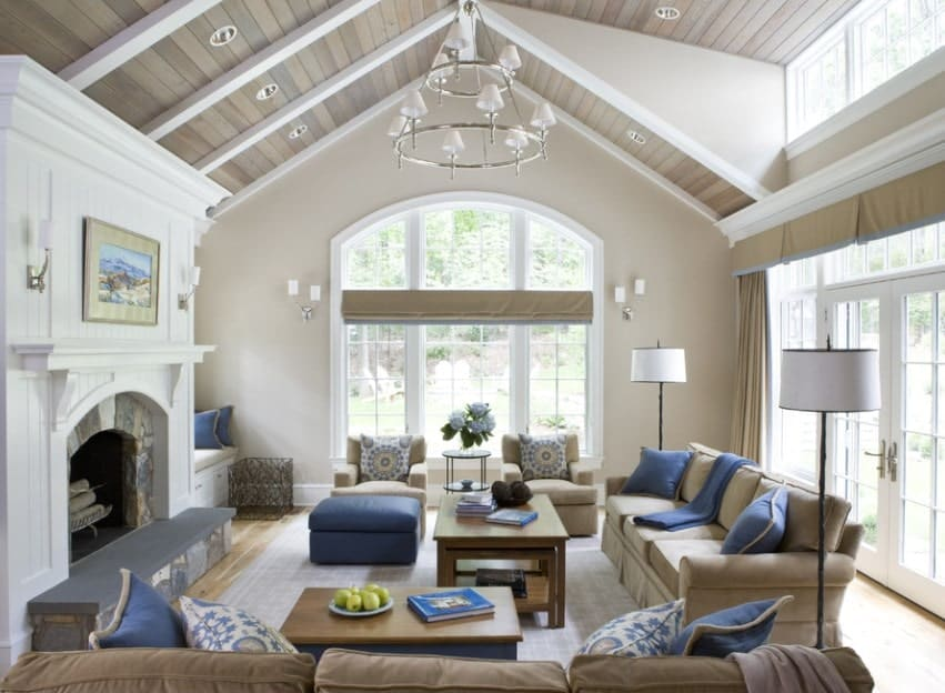 This living room offers classy seats set on a gray rug. The beige walls are perfect together with the wooden ceiling lighted by a glamorous chandelier.