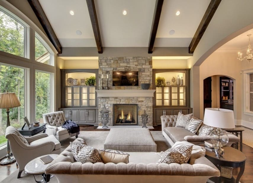 Large living room featuring cozy seats on top of a simple rug. There's a fireplace nearby with a TV on top. The beams on the ceiling add style to the home's living space.