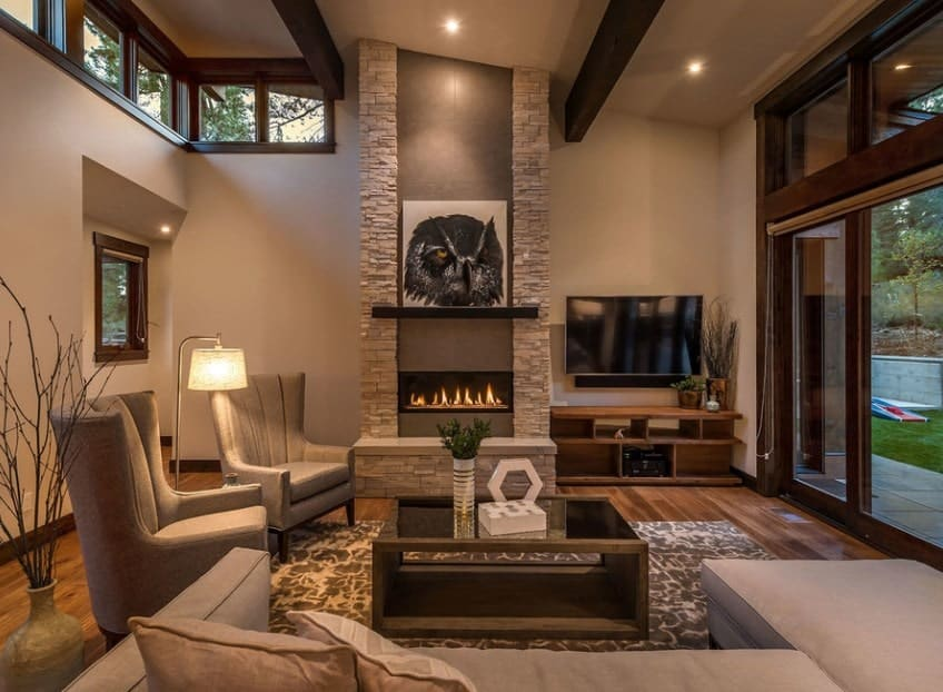 This living room looks so stylish with its beige walls, hardwood flooring, and sofa set. The fireplace with an enchanting wall decor looks stunning.