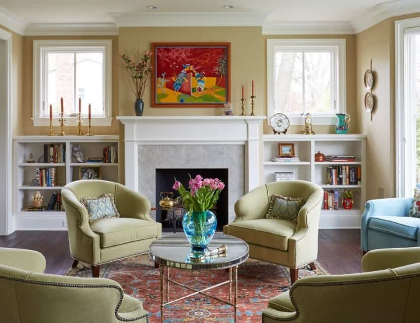 This living room offers cozy seats and a lovely rug near the stylish fireplace. There are shelves on both sides of the fireplace.
