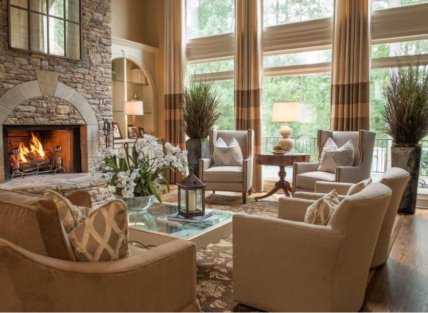 This living room offers a nice set of seats near the fireplace. The rug looks so classy while the tall ceiling adds elegance to the home.