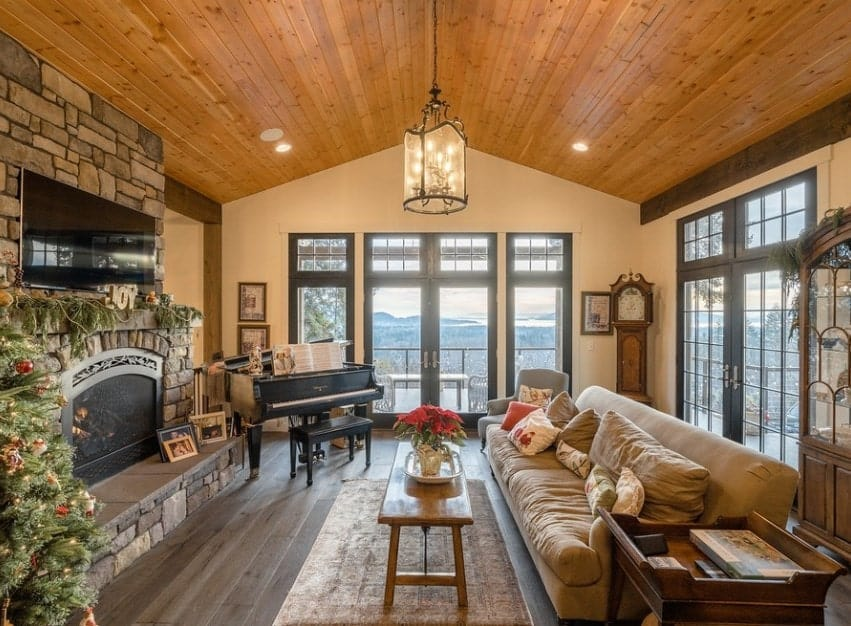 A large living room with a rustic finish on the hardwood flooring, vaulted ceiling and fireplace. The glamorous ceiling lights shower down the brightness to this gorgeous living space.