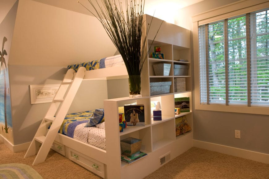 This is a clean and cozy boys bedroom with a stark white wooden bunk bed that has a built-in shelving on the side that can be a useful storage for various items. The structure is complemented by the beige carpeted flooring as well as the gray walls.