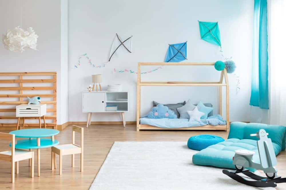 Large boy's bedroom with elegant blue-green color shade. The room also features hardwood flooring and white walls.