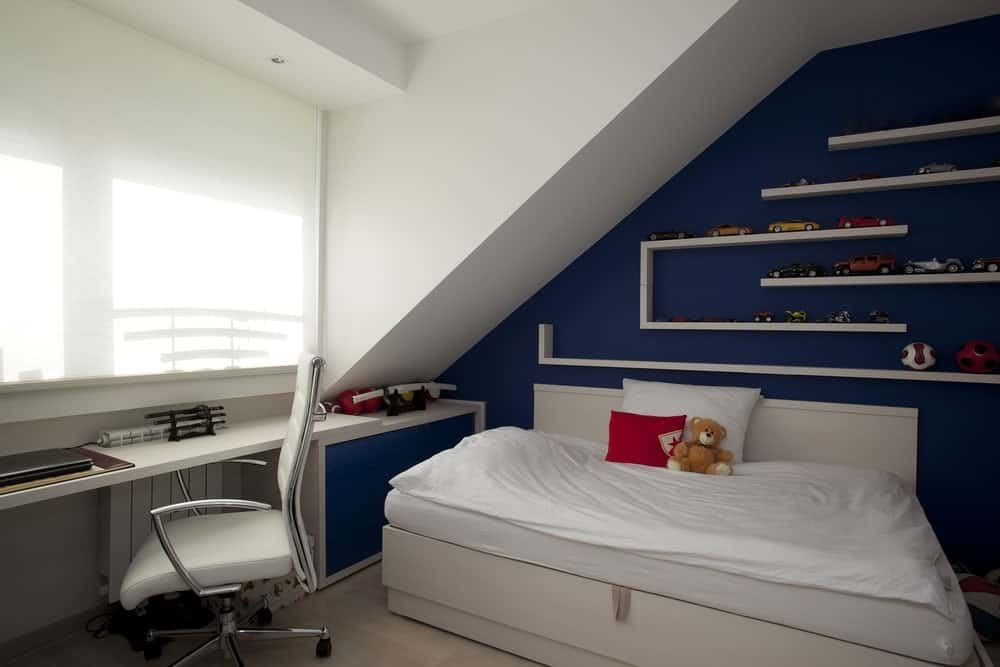This boy's bedroom boasts a stylish wall with interesting shelves. The white and blue color combination looks so cool for this room.