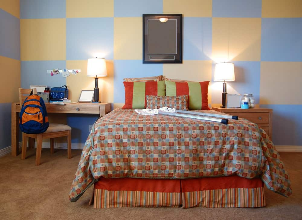 This boy's bedroom boasts colorful walls with tiles design, along with carpet flooring and a pair of table lamps.
