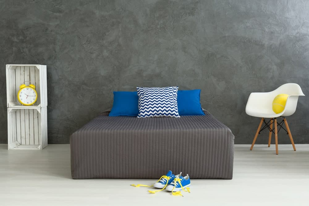 A close up shot at this boy's bedroom's gray bed matching the gray walls and floors.