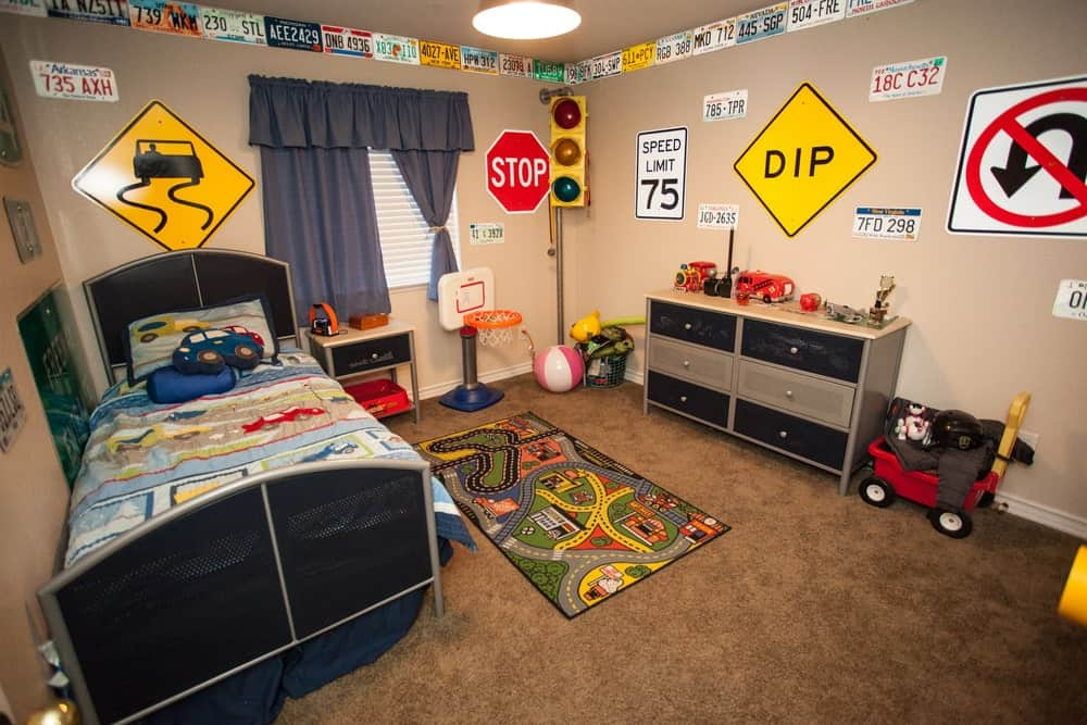 A boy's bedroom with carpet flooring and multiple road signs wall decorations, perfect for a car lover little man.