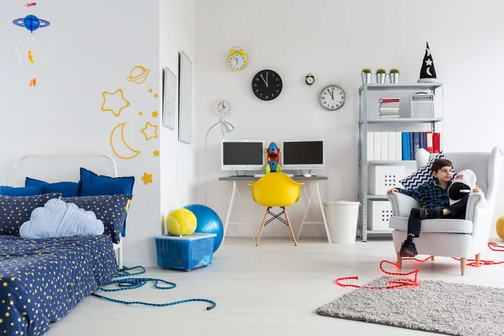 Large boy's bedroom featuring white walls and floors along with a blue bed. The computer table looks modish, together with the shelving on the side.