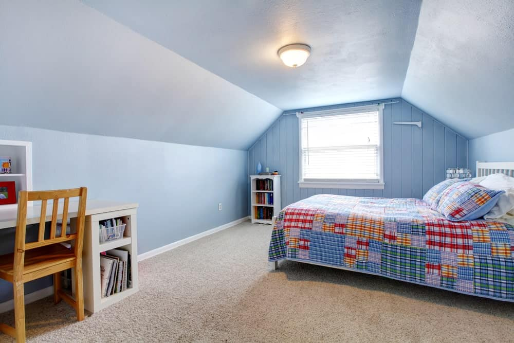 A blue boy's bedroom with carpet flooring and charming ceiling light. There's a study desk on the side.