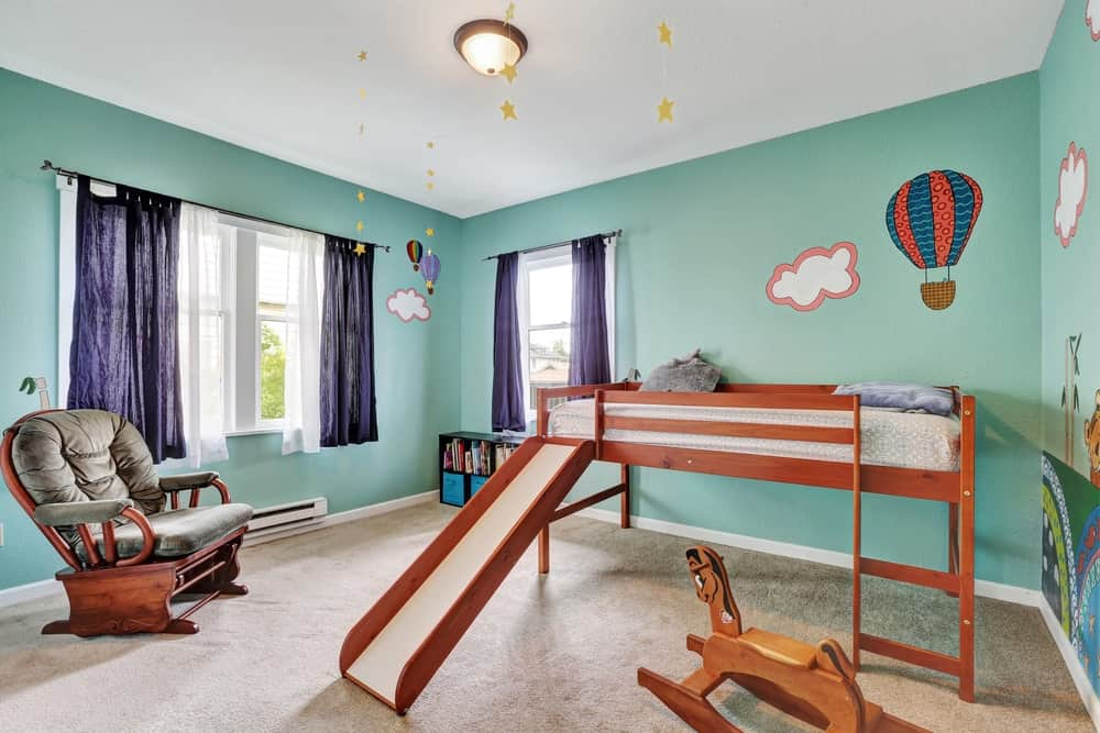 This little boy's bedroom features green walls with cute designs and a bed with a built-in slide leading to the carpet flooring.