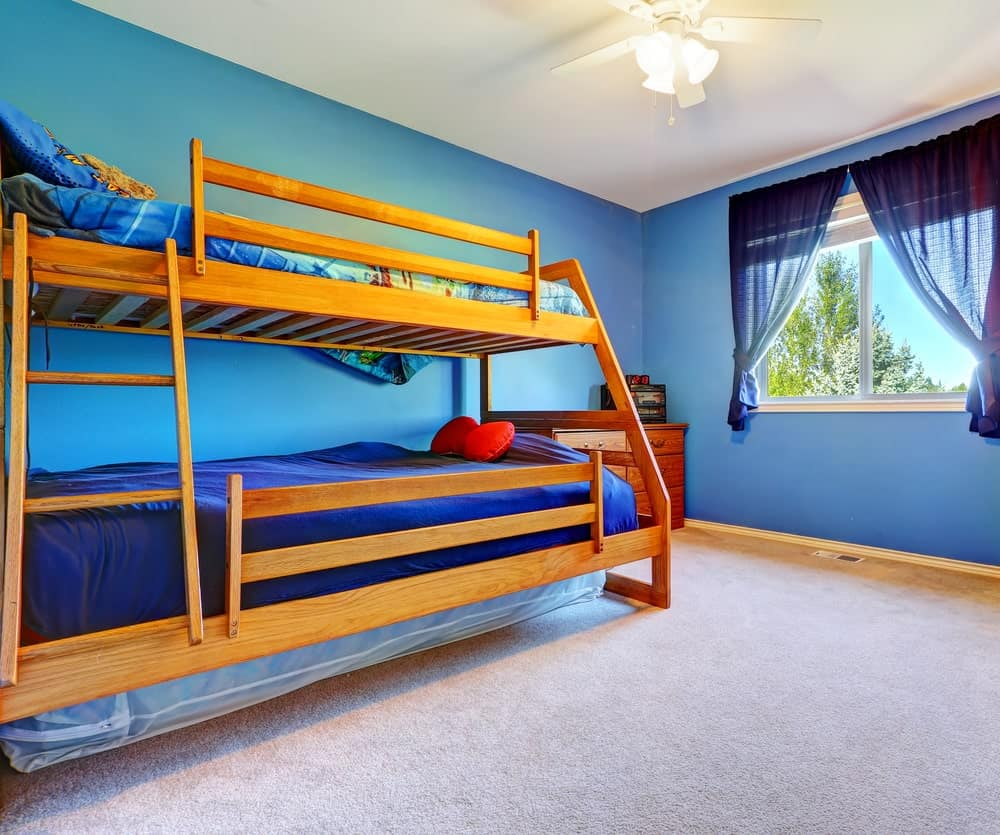This boy's bedroom boasts blue walls and window curtains, along with the carpet flooring and a bunk bed lighted by a charming ceiling lighting.