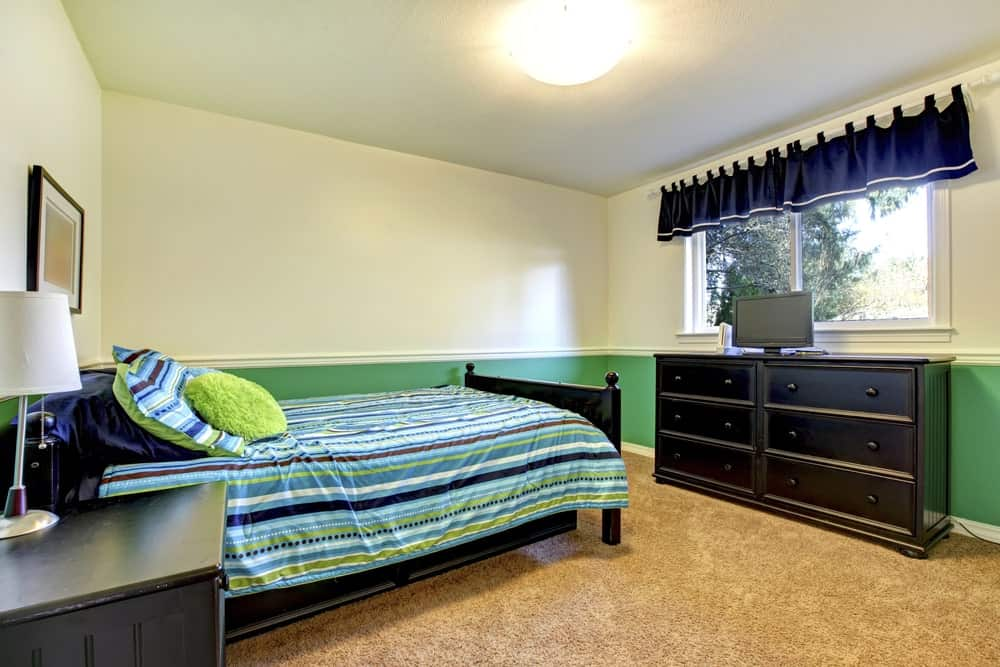 This boy's bedroom boasts white and green walls paired with espresso finished bed frame and cabinet set on the carpet flooring.