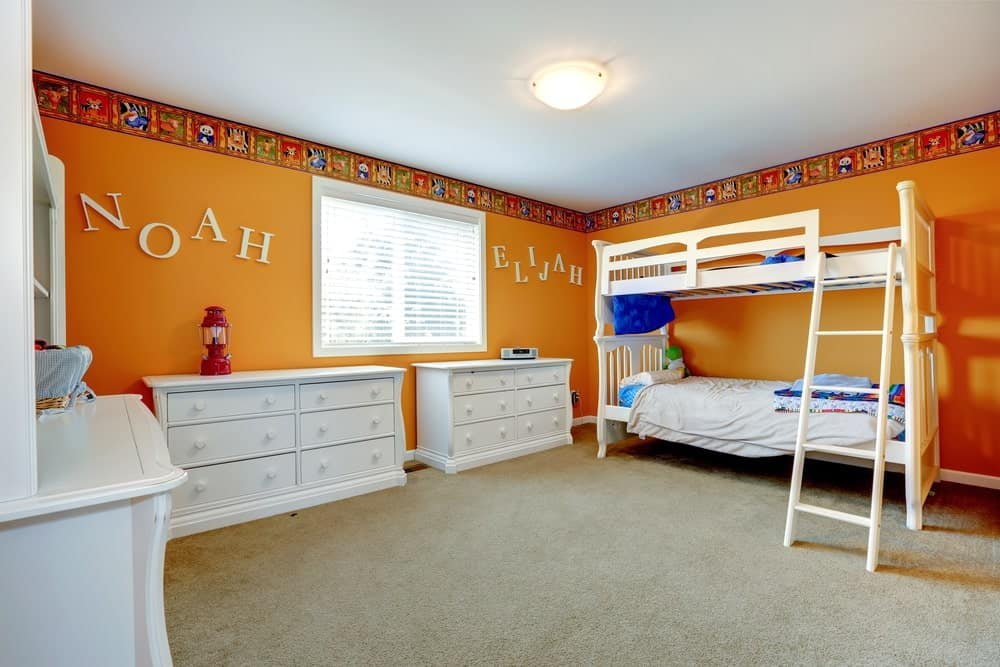 An orange boy's bedroom with white cabinets, table and bunk bed frame, all set on the carpet flooring.