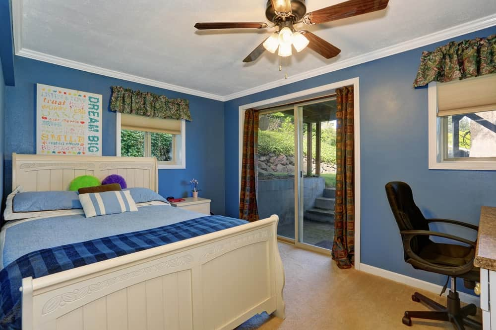 Small boy's bedroom with blue walls, white bed and ceiling and a small study desk on the corner.