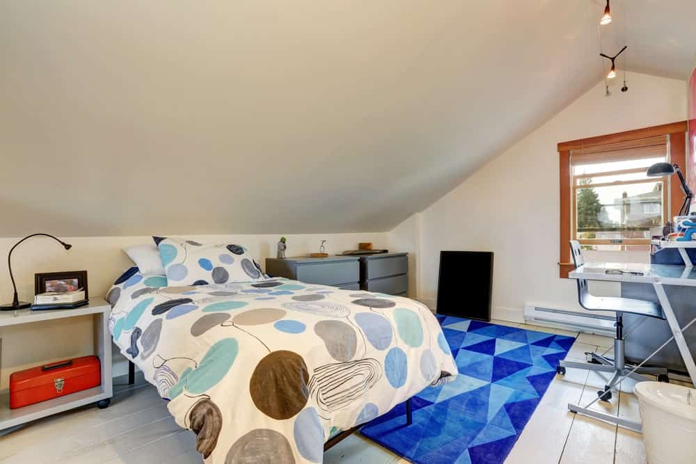 This boy's bedroom features a shed white ceiling matching the white hardwood flooring topped by a stylish blue rug.