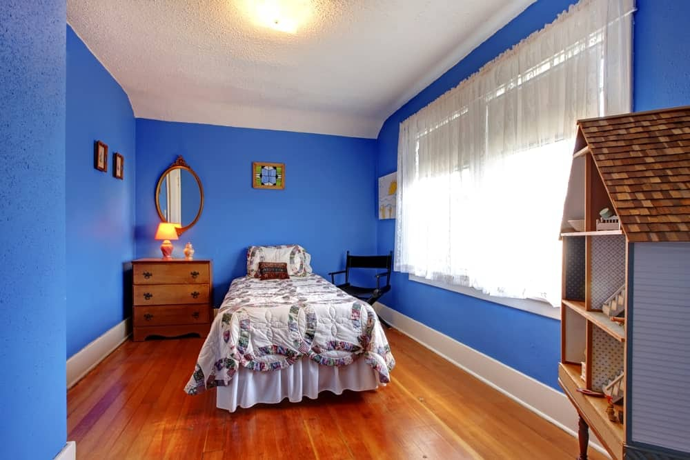 A blue boy's bedroom featuring cherry-finished hardwood flooring and white window curtains.