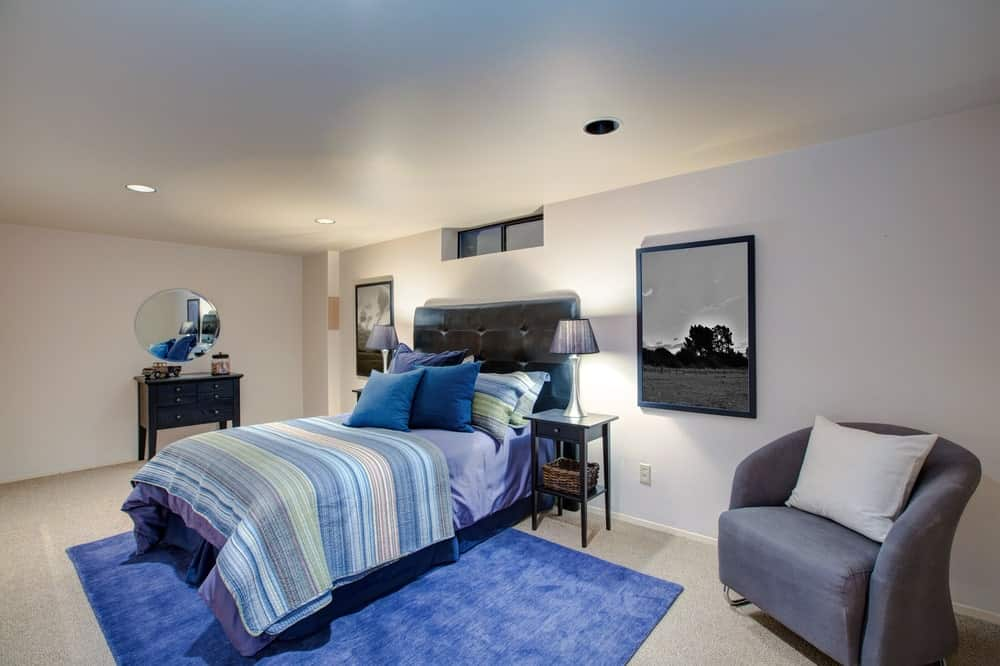 A modish boy's bedroom with white walls, ceiling and carpet flooring topped by a blue rug that matches the bed perfectly. The wall decors look perfect together with the gray seat on the side.