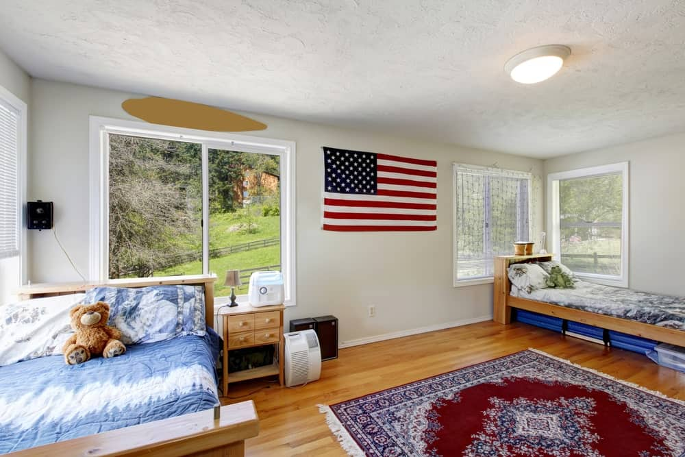 Large boys' bedroom surrounded by white walls with the U.S. flag as wall decor. The hardwood flooring topped by a rug looks classy.