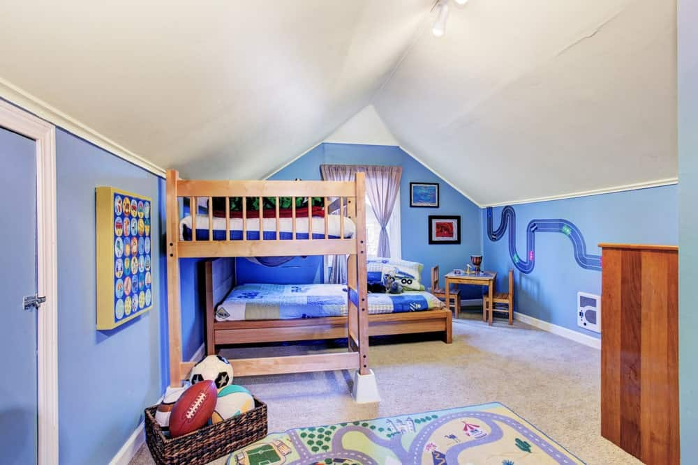 Large boy's bedroom with blue walls and white vaulted ceiling, along with the carpet flooring topped by a cute rug.