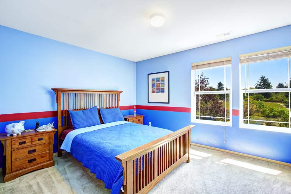This boy's bedroom features blue walls with red accent. The windows overlook the beautiful outdoor space. The carpet flooring adds class to the room.