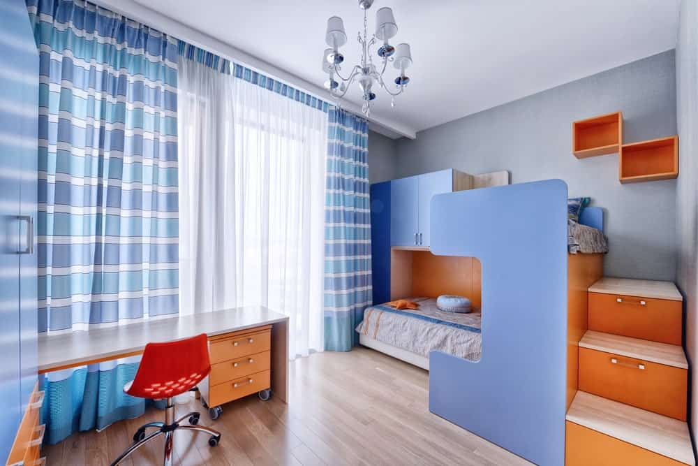 This boy's bedroom boasts a stylish bunk bed with stairs, along with a stylish study desk set on the hardwood flooring and surrounded by gray walls. The curtains look very lovely.