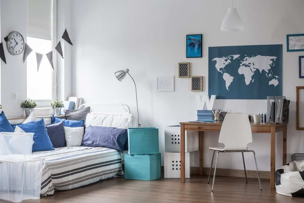 This boy's bedroom features white walls with a world map decor near the study table set on the hardwood flooring.