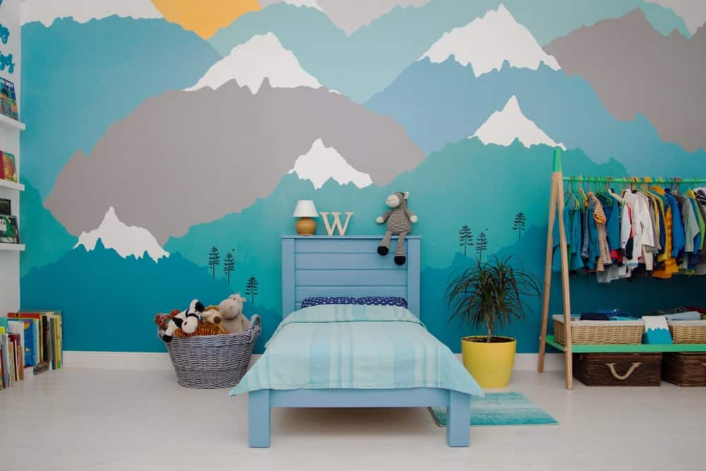 A little boy's bedroom featuring interesting wall design and smooth flooring.