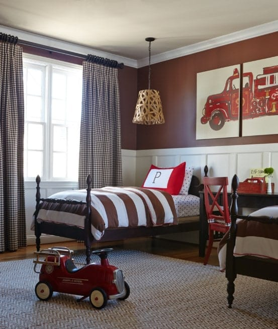 This boy's bedroom features brown and white walls with firetruck wall decor. The bed is lighted by a charming pendant lighting.