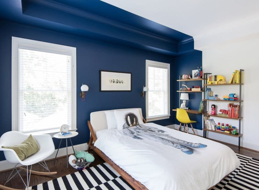 Large boy's bedroom with white and blue walls, along with a nice rug set on the hardwood flooring.