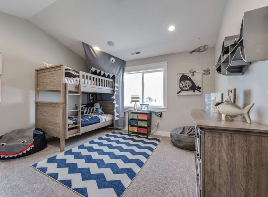 Large boy's bedroom with white walls and gray carpet flooring with the blue and white rug. The rustic bunk bed and table look stylish.