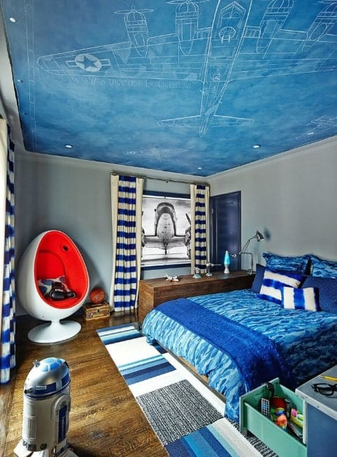 Small but very stylish boy's bedroom with a blue sky-inspired ceiling with a plane design. The hardwood flooring looks perfect with this room.