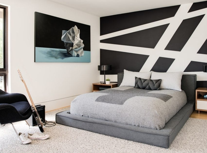 This boy's bedroom boasts stylish walls and bed, along with charming wall decor.