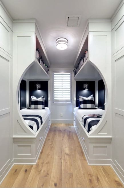 This boy's bedroom boasts stylish beds with elegant-finished walls and hardwood flooring.