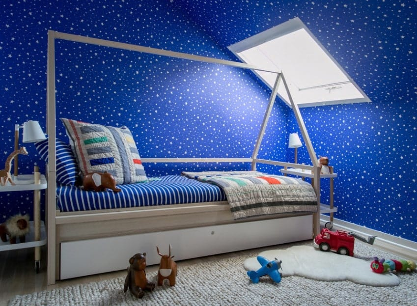 This boy's bedroom boasts galaxy-inspired walls. The bed looks great together with the room's style as well.