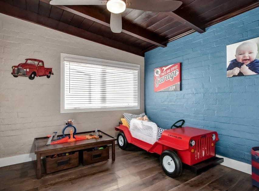This boy's bedroom features a vehicle-designed bed set on the hardwood flooring, surrounded by white and blue walls.