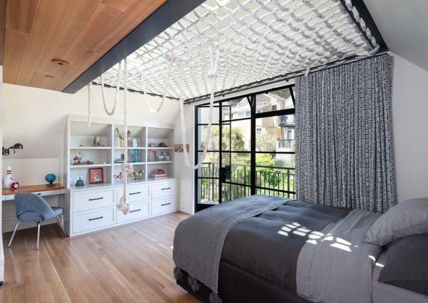 Large boy's bedroom with black and gray bed, matching the window curtain. There's a doorway leading to the home's balcony.