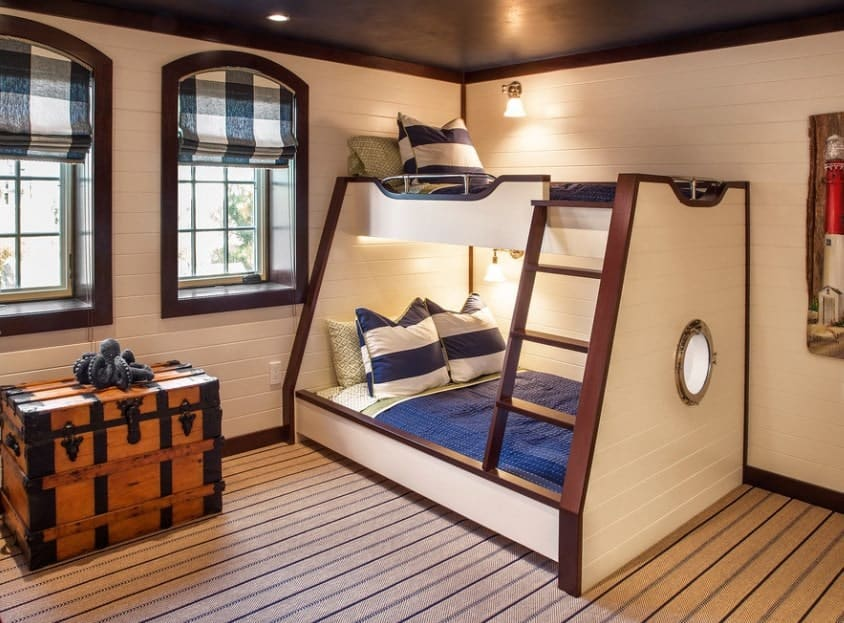 This boy's bedroom features a stylish bunk bed lighted by wall lights. The carpet flooring looks classy too.