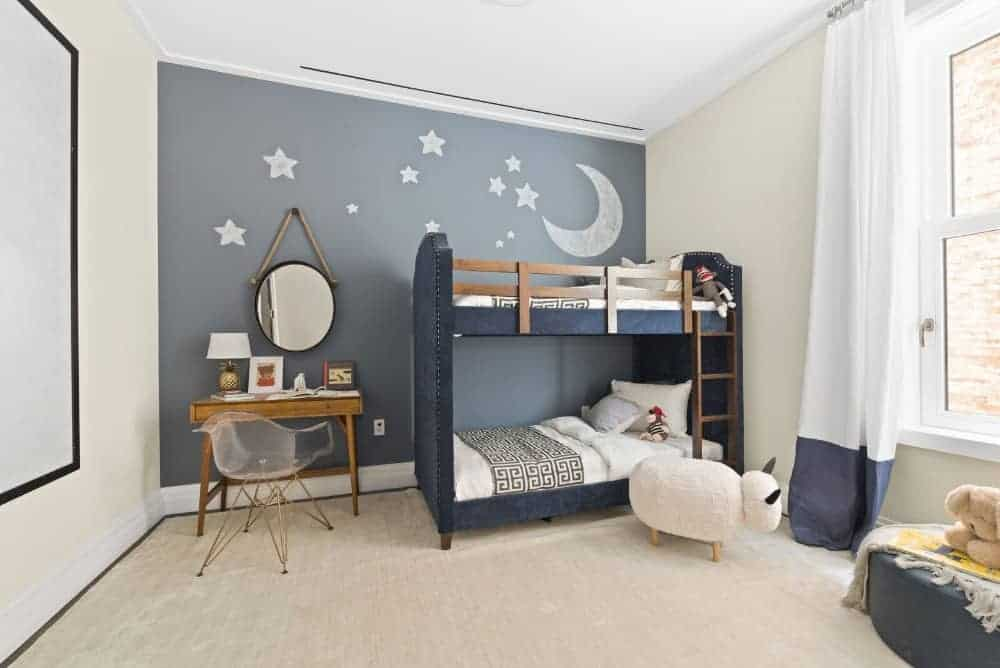 The moon and stars mural sets a serene backdrop to the blue denim bunk bed and wooden vanity that's paired with a modern glass chair. This boys bedroom is surrounded by beige walls that are complemented with a matching carpet.