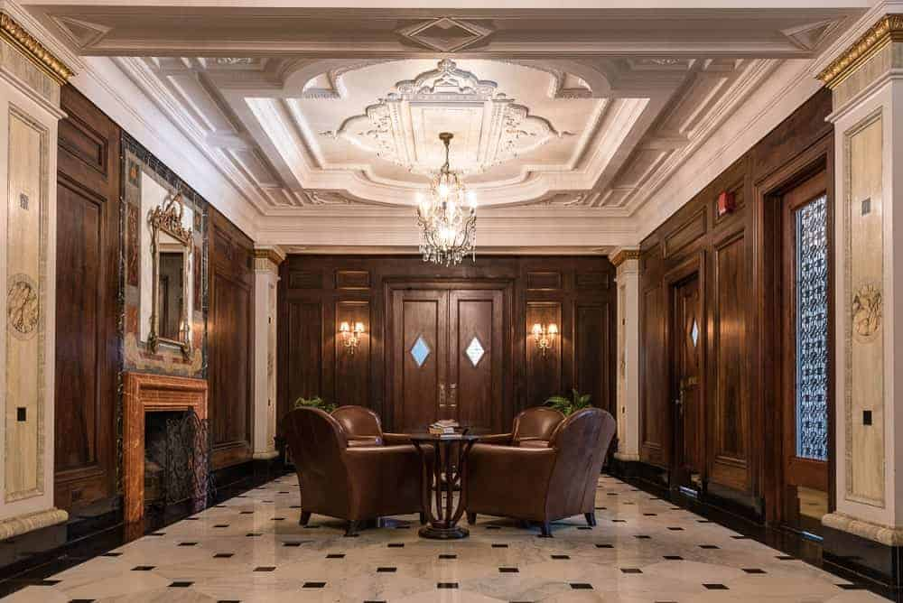 This foyer oozes with luxury and style and warmed by the fireplace with a wooden mantle that complements the dark brown wooden walls. These are paired well with the brown leather cushioned armchairs surrounding the central table in the middle of the beige marble flooring.